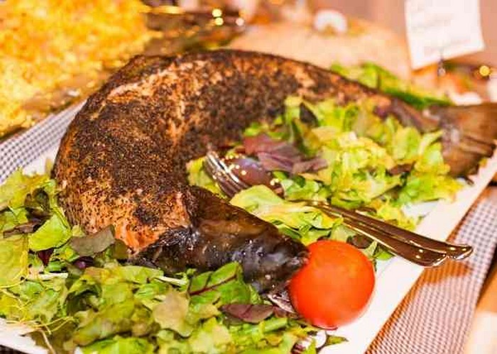 Whole baked salmon stuffed with lemon and herbs, vegetables